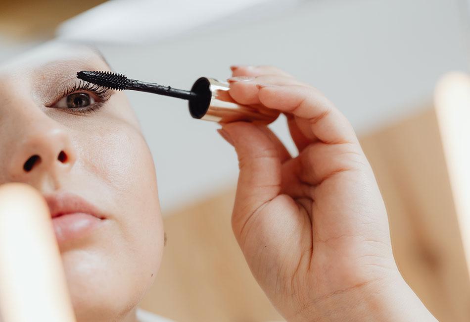 Frau trägt Drogerie Mascara auf
