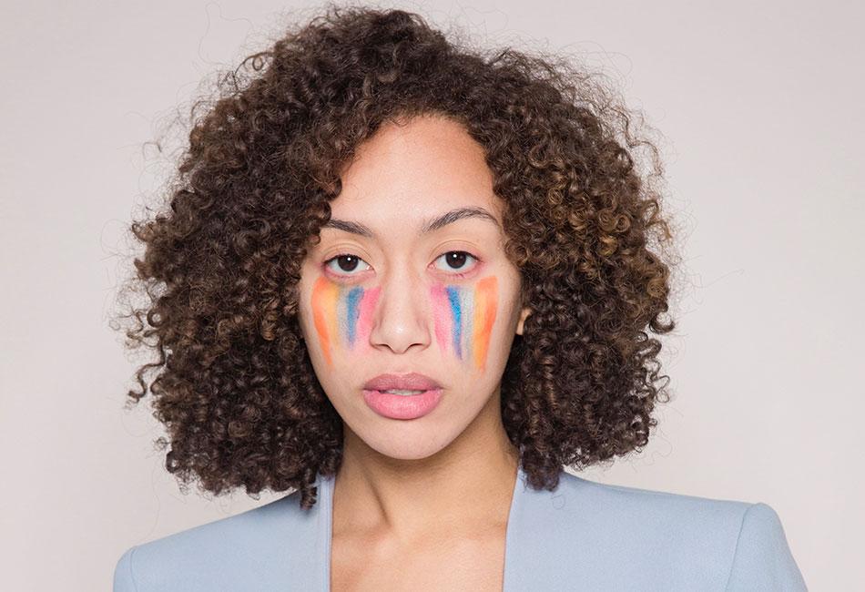 Frau mit Regenbogenfarben im Gesicht