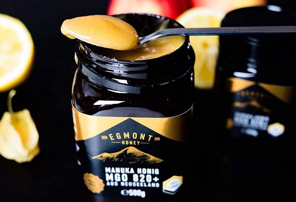 Glas mit Manuka-Honig und Löffel