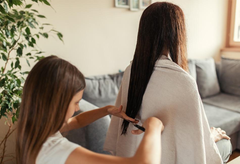 Zwei Frauen, die sich selber die Haare schneiden