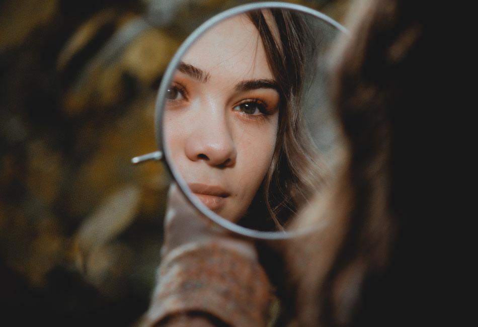 Frau schaut in Kosmetikspiegel