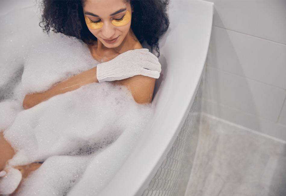 Frau in Badewanne mit Peelinghandschuh