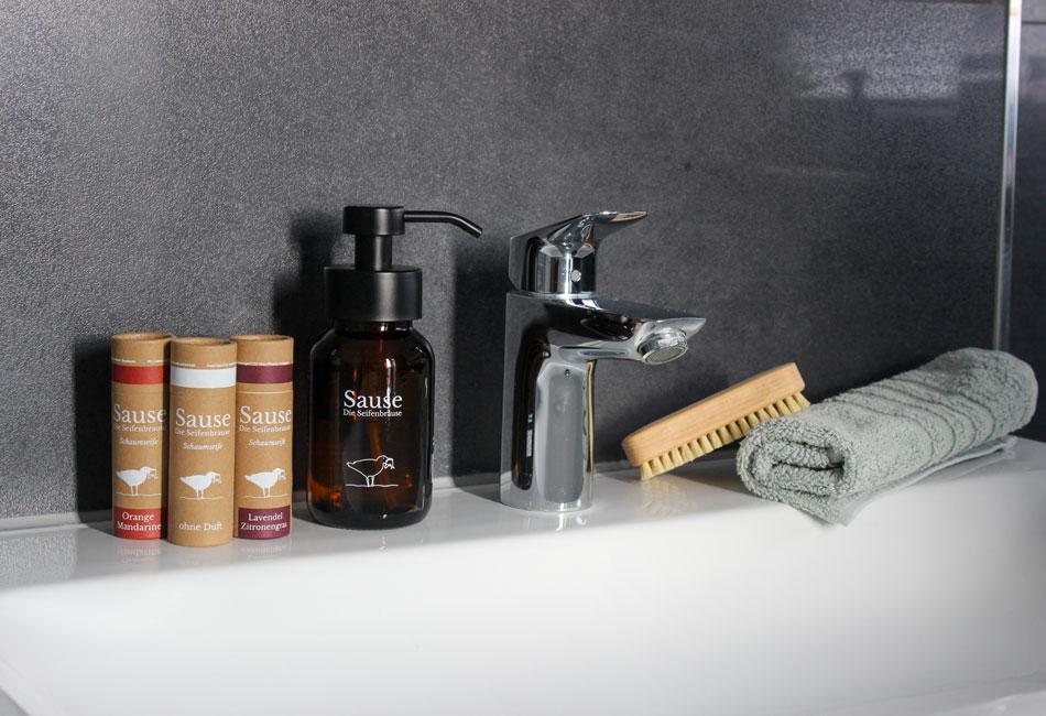 Sause Seifenspender und Verpackungen mit Tabletten auf Waschbeckenrand