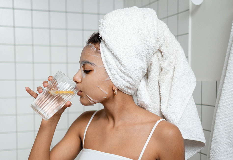 Frau mit Tuchmaske trinkt Wasser